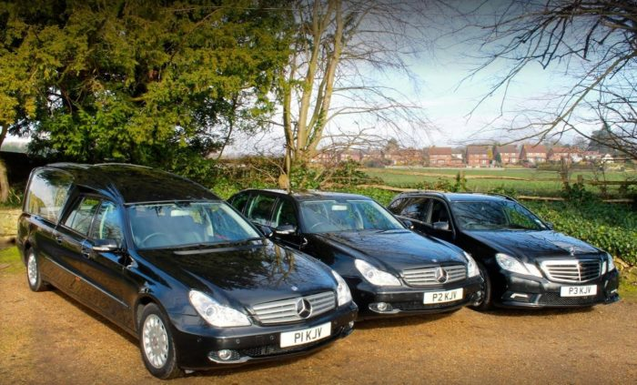 Three black Mercedes funeral vehicles; one hearse, one limousine and one estate car