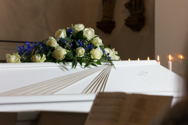 Bouquet of white flowers resting on a white wooden coffin