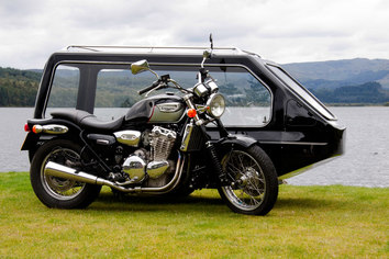 Black motor cycle hearse in front of a lake