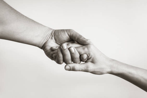 Black and white image of two hands caringly hold one another