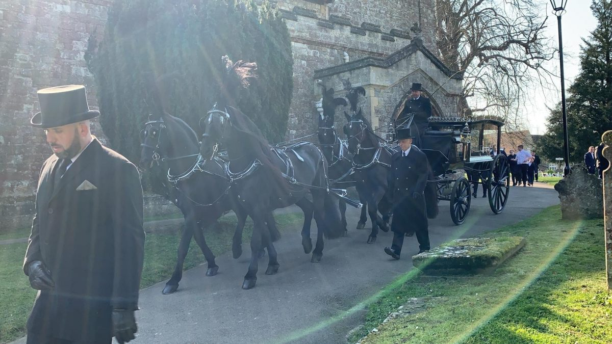 Black horse drawn carriage funeral leaving a church