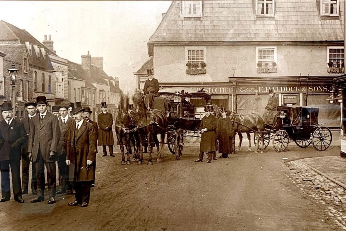 Old photograph taken in 1905 of two traditional horse drawn carriages surrounded by well dressed men