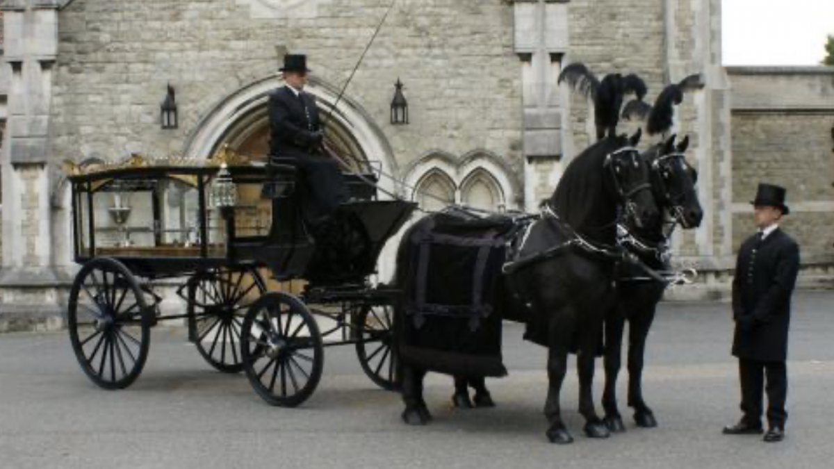 Traditional horse drawn funeral carriage. Two black horses with decorated in large black feathers and two undertakers dressed in black with top hats.