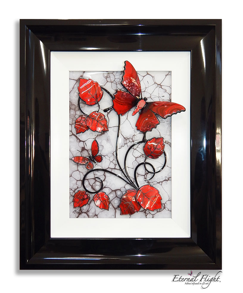 Black framed artwork of red butterflies and leaves against a white background